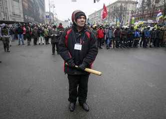 An anti-government protester stands guard near barricades in Kiev