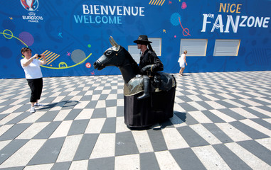 A tourist takes a photo of a street artist wearing a 'Zorro' costume as he walks past a fan zone before the start of the UEFA 2016 European Championship in Nice