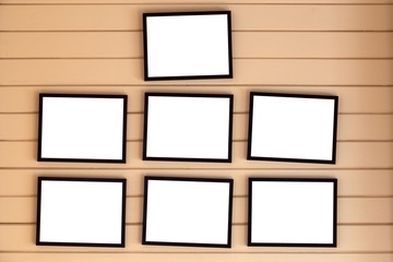 frames hanging on a plank wooden wall. White mock up for designers.