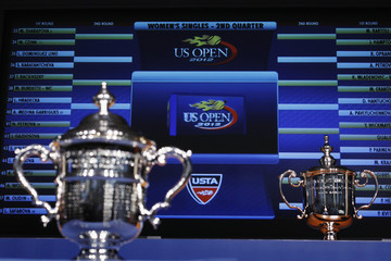 The men's and women's singles trophies rest in front of a television screen during the US Open tournament draw ceremony in New York
