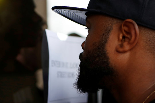 A demonstrator stands in front of the East Baton Rouge Parish City Hall doors in Baton Rouge, Louisiana