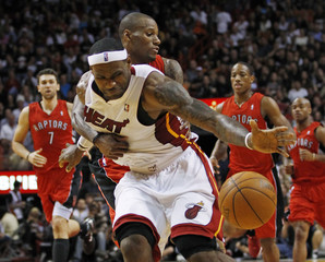 Heat's James is fouled by Raptors' Weems during NBA basketball action in Miami