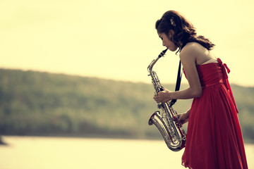 Woman playing saxophone sax at sunset,Saxophonist woman in red dress