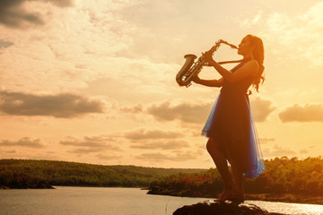 Woman playing saxophone sax at sunset
