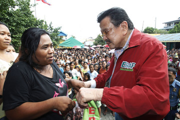 Former Philippine President Joseph Estrada distributes relief goods to a typhoon victim at Baseco in Tondo city