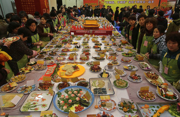 Neighbourhood residents stand around a table full of home-made dishes and a miniature replica decoration of the Tiananmen gate in the middle, during an annual local celebration for the upcoming Chinese New Year in Wuhan