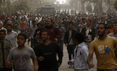 Protesters who oppose Mursi flee from riot police during clashes along streets which lead to the Muslim Brotherhood's headquarters in Cairo