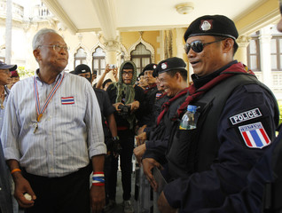 Thaugsuban speaks with riot policemen during a rally at the Government House in Bangkok