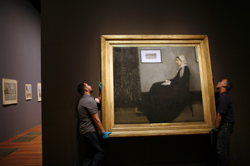 "Workers hang the painting of U.S. artist James McNeill Whistler titled ""Whistler's Mother,"" at the deYoung Museum in San Francisco"