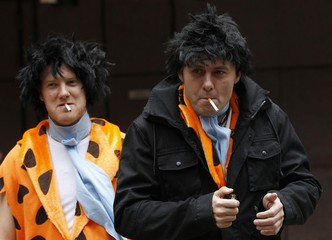 Two men dressed as cartoon character Fred Flintstone smoke cigarettes as they wait for Britain's Prince Charles and Prince William to leave a charity event in London