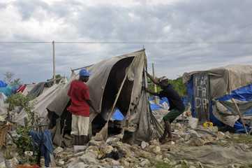 Haitians living in a tent camp built for people affected by the January 2010 earthquake try to repair their tent that was destroyed after Tropical Storm Isaac swept through Port-au-Prince