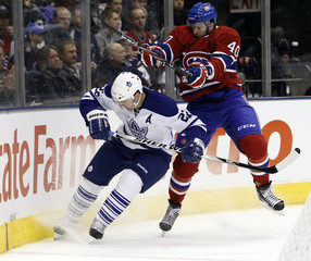 Maple Leafs defenseman Beauchemin is checked by Montreal Canadiens forward Lapierre during their NHL hockey game in Toronto