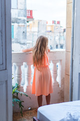 Little girl on old balcony in apartment looking on the street in Old Havana, Cuba.