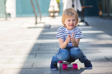 Adorable kid outdoors. Cute pretty child smiling at camera. Casual boy on summer time skating on a skateboard. thumb up