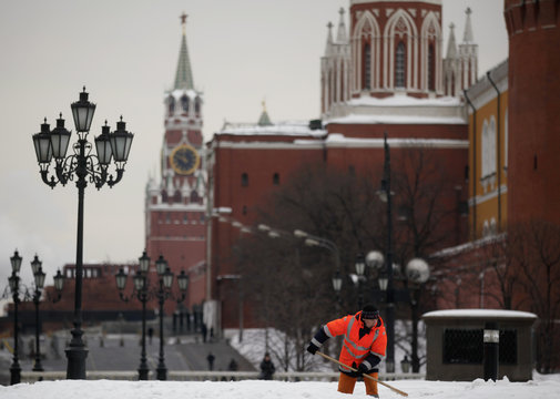 A worker shovels snow, with the Kremlin seen in the background, in central Moscow