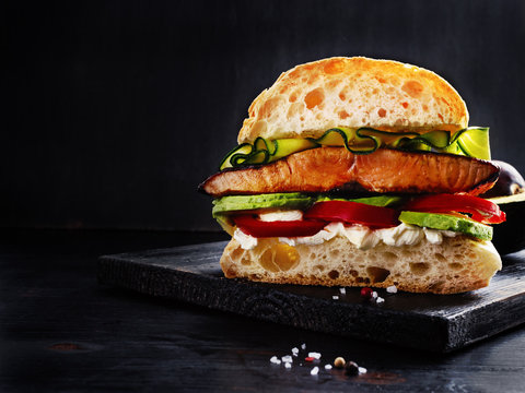 Ultimate sandwich with grilled salmon, cream cheese, sliced avocado and seasonals on black wooden board with free text space.