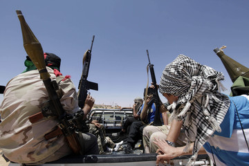 Rebels sit at the back of a truck in the village of Al-Qawalish