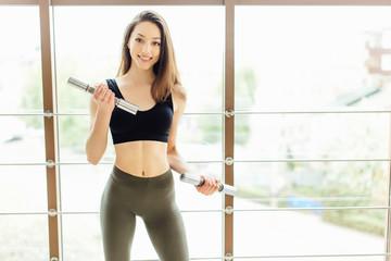 Sporty girl do exercise for biceps on white background