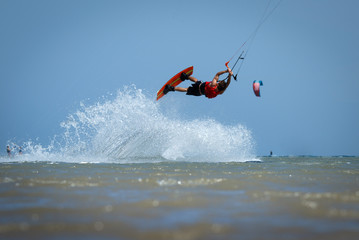 Recreational water sports: kite surfing. Kite boarding sportsman jumping high in the sky on windy day