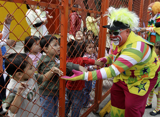 A clown greets children through a fence of a garden as he takes part in an annual pilgrimage at the Basilica of Guadalupe in Mexico City
