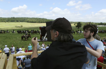 Photographer Richard Barnes photographs a battlefield with an antique wet plate camera during re-enactment activities July 5, 2013 recognizing the 150th anniversary of the US Civil War battle in Gettysburg Pennsylvania