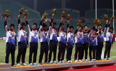 South Korea's men's rugby team celebrate on the podium after winning their bronze medal Rugby Sevens match against China at the 16th Asian Games in Guangzhou