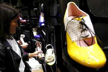 File picture of Carmen Dang, a design consultant, checking a display showcasing designs of shoes located in a department store in central Sydney, Australia