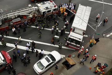 New York City firefighters and Metropolitan Transportation Authority (MTA) workers attend an emergency during a derailed F train in Woodside, New York