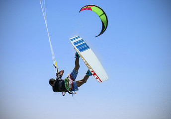 Recreational water sports: kitesurfing. Kiteboarding sportsman jumping high in the sky on windy day. Extreme sports action with wind and water. Healthy active lifestyle.Summer fun adventure and hobby.