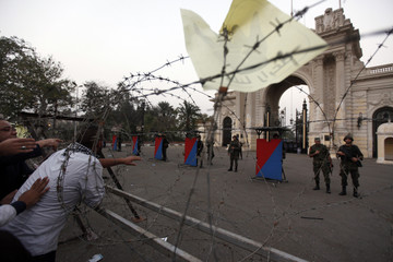 A supporter of ousted Egyptian President Mohamed Mursi attempts to speak to Republican Guard soldiers as he reaches through a barb wire barricade as Muslim Brotherhood supporters gather to protest in support of Mursi in front of the Qubba Palace in Cairo