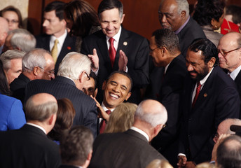 U.S. President Barack Obama laughs as he chats with members of Congress as he arrives to deliver his State of the Union address to a joint session of Congress on Capitol Hill in Washington
