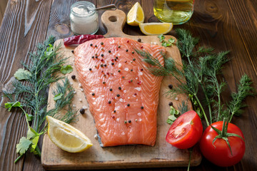 Fresh salmon fillet with aromatic herbs, spices, mushrooms, lemon and cutting board on wooden background. Top view. Closeup.