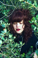 Mujer joven dormida entre ramas y hojas en un bosque