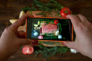 woman hands taking picture of fresh salmon, herbs, spices and vegetables