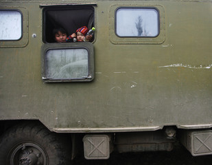 Mongolian child and a baby look out of the window of an old Russian military truck at the foot of Khorgo volcano, in Arkhangai province