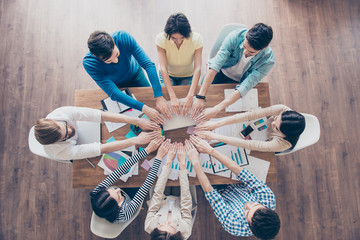 All for one! And one for all! Top up of colleagues putting their hands next to each other in a circle at their work place. All are wearing casual clothes.Team work and success concept