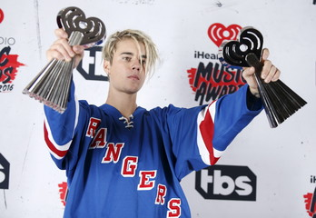 """Recording artist Justin Bieber poses with his Dance Song of The Year Award for """"Where Are U Now"""" and Male Artist of the Year Award backstage at the 2016 iHeartRadio Music Awards in Inglewood"""