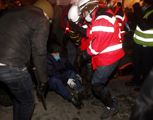 Medical volunteers help an anti-government protester at the site of clashes with riot police in Kiev