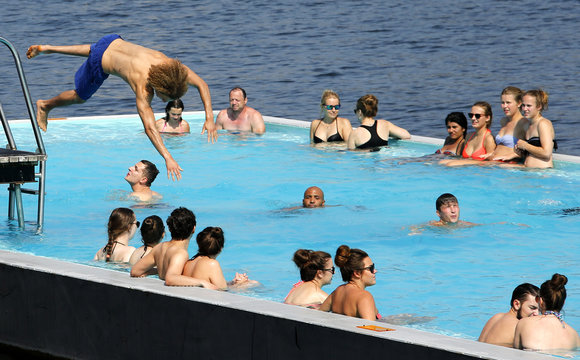 A man jumps into a floating swimming pool anchored on the bank of Spree river in Berlin