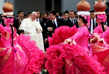 Pope Francis talks with Paraguayan President Cartes as dancers perform after his arrival at the international airport in Asuncion