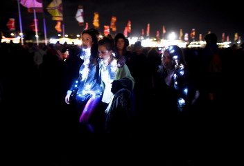 Revellers are lit up as they walk through Worthy Farm in Somerset during the Glastonbury Festival