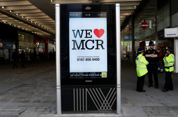 Police officers chat next to a sign in central Manchester