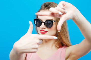 Amazing Brunette Model in Fashionable Sunglasses and Pink Dress is Having Fun in Studio on Blue Background.