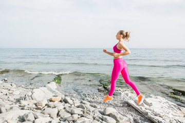 Young sporty woman in pink uniform outdoors. Fitness girl running on beach