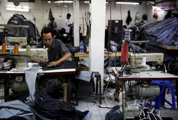 A worker stitches a pair of jeans at a small factory at Cakung industrial village in Jakarta