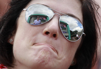 An image of Britain's Andy Murray on a large screen is reflected in the sunglasses of a spectator watching on Henman's Hill the men's semi-final match between Murray and Spain's Rafael Nadal at the 2010 Wimbledon tennis championships in London