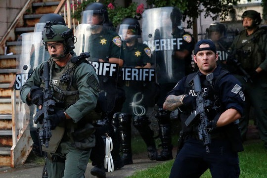 File photo of law officers marching down a street during protests in Baton Rouge