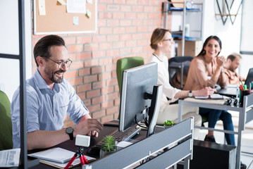Hilarious smiling office worker among coworkers
