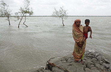 Nasiran stands on a river dam with her grandson, as she describes the devastation of cyclone Aila, in Gabura