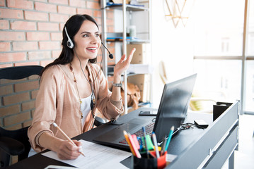Cheerful female worker using earphones